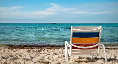 Empty beach chair near clear blue ocean.