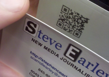Photograph, taken in front of a mirror, of the front and back side of a business card, with a QR two-dimensional barcode on the back.